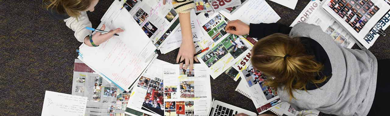 Students Working on High School Yearbook Designs with Jostens
